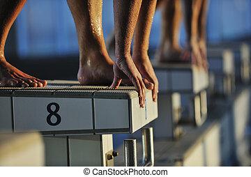 young swimmmer on swimming start - start position race...