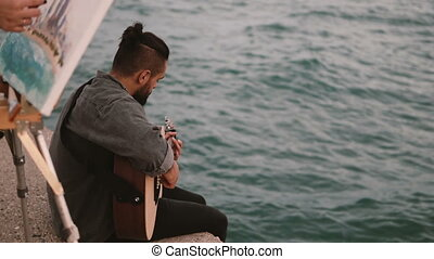Young talented couple sitting on the shore of the sea and doing hobby. Woman drawing, man playing guitar.