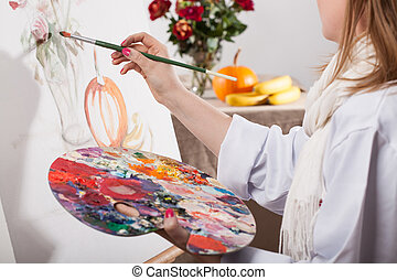 Young talented woman painting a nature on white canvas