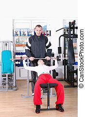 man assisting woman weight lifting at a gym