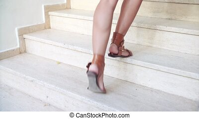 young tanned female feet in sandals go up stairs in summer....