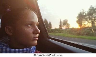 Young tanned woman enjoys the view from a car while...