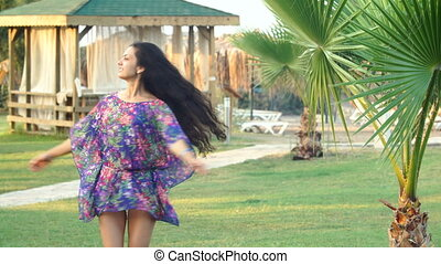 young tanned woman with long hair dancing between tropical palm trees in summer