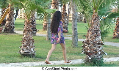 young tanned woman with long hair walks along path between tropical palm trees