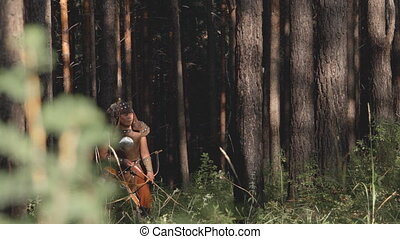 Young Tatar mongolian archer shoots bow, standing in green...