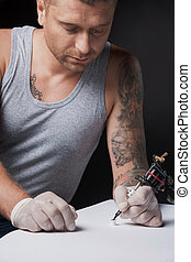 young tattooist drawing picture on paper. young man looking at ink gun