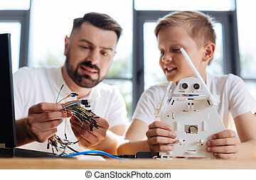Young teacher helping his student with robot construction