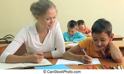Young teacher sitting by her pupil and helping him