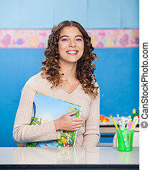 Young Teacher With Book Sitting At Desk