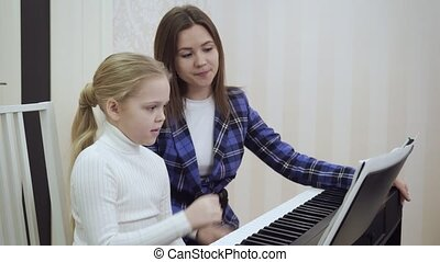 Young teacher with little cute girl playing on the electric piano.