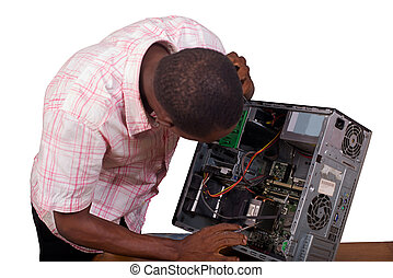 Young technician looks at and repairs a broken computer