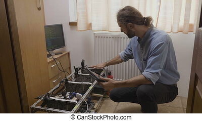 Young technician setting up gpu mining rig measuring...