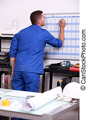 young technician writing on a calendar