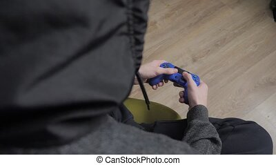 young teen and joystick man hooded sweater absorbed In...