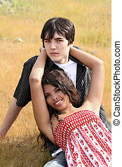 Young teen boy and girl outdoors reclining