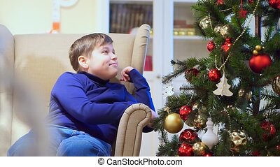 Young teen boy sitting in a chair near the Christmas tree. He looks at the toys, hang on the Christmas tree