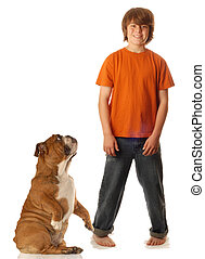 young teen boy standing beside dog that is begging at his...