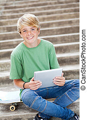 young teen boy using tablet computer
