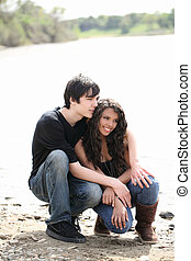 Young teen couple outdoors by river jeans