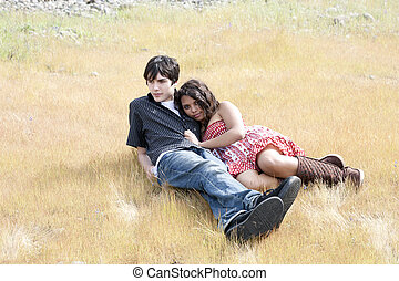 Young teen couple reclining outdoors in yellow grass