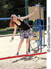 Young teen girl balancing on red bar