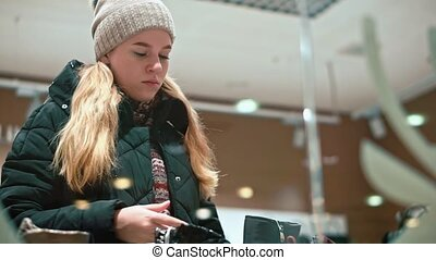 Young teen girl chooses her shoes in the store.