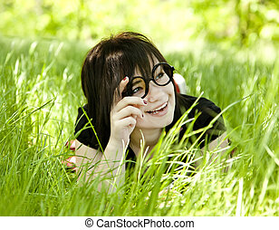Young teen girl in glasses at green grass.