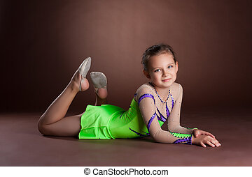 Young teen girl in green gymnast costume posing
