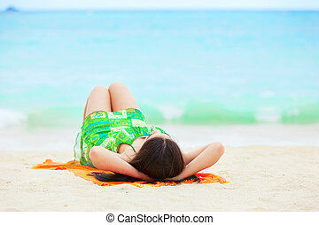 Young teen girl lying on back at tropical beach
