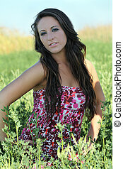Young teen girl outdoor amid green plants in dress