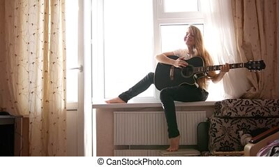 Young teen girl playing acoustic guitar at home