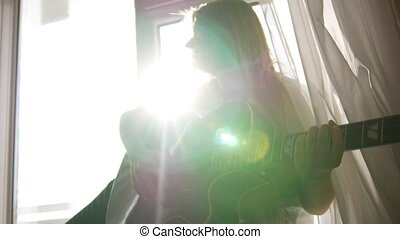 Young teen girl playing acoustic guitar at home, close up