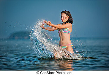 Young teen girl playing with waves