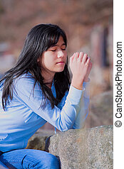 Young teen girl sitting outdoors on rocks praying
