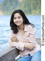 Young teen girl sitting quietly on lake pier, relaxing