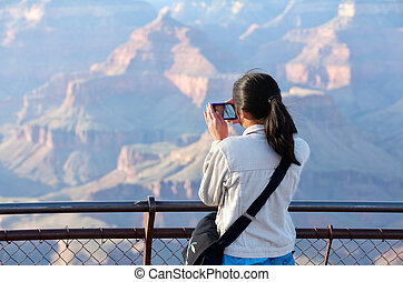 Young teen girl standing at railing taking pictures at Grand Canyon