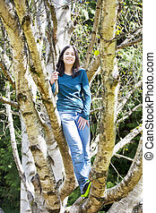 Young teen girl standing on branches in birch tree, smiling