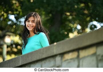 Young teen girl standing on bridge
