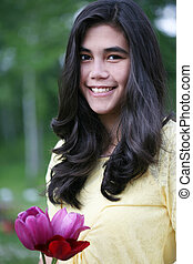 Teen girl standing with tulips