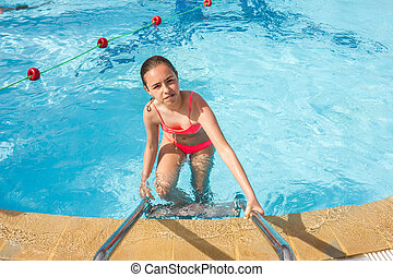 Young teen girl swims and have fun in the outdoor pool