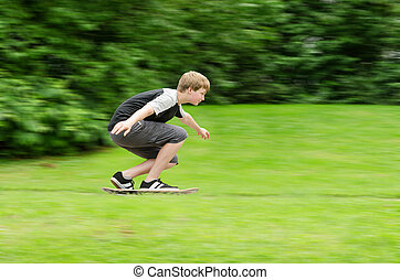 Young teen guy fast rides a skateboard in park