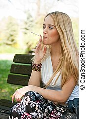 Young teen person smoking cigarette outdoors