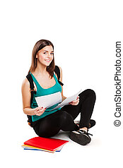 Young teen student sitting on floor with backpack reading a...