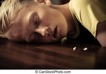 Young teenage boy drug addict passed out with his head on...