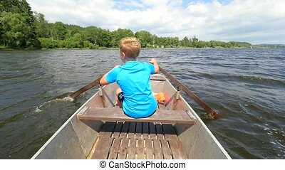 Young teenage boy rowing a rowboat or paddle boat on a lake ...