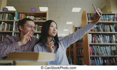 Young teenage couple of students sitting at table in library...
