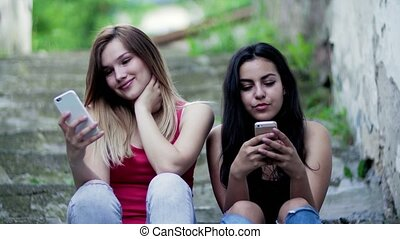 Young teenage female friends sitting outdoors in town, using...