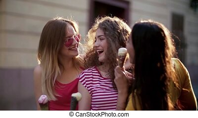 Young teenage female friends with ice cream standing...