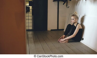 Young teenage girl dancer crying after loss perfomance sits on floor in hall indoors