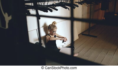 Young teenage girl dancer crying and tearing book sits on floor in hall indoors